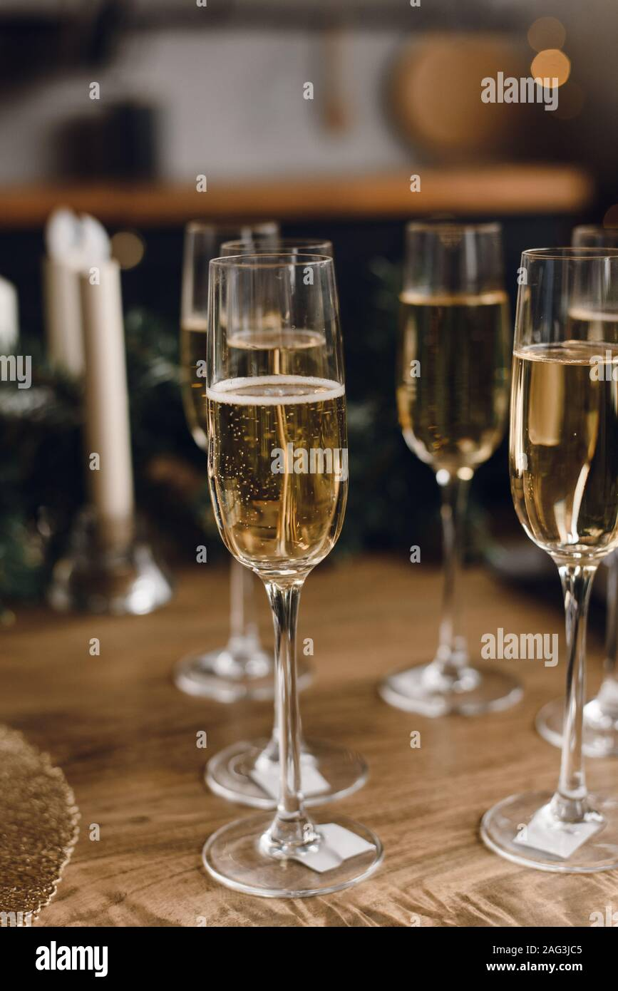 Group of glasses of luxury champagne on a wooden table. White wine in glasses of champagne against the background of a Christmas tree and garland ligh Stock Photo