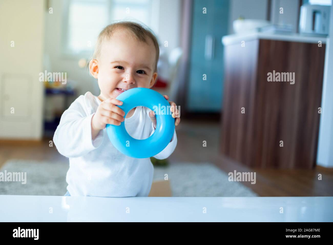 Caucasian baby girl standing next to table with blue torus in hands and laughing Stock Photo