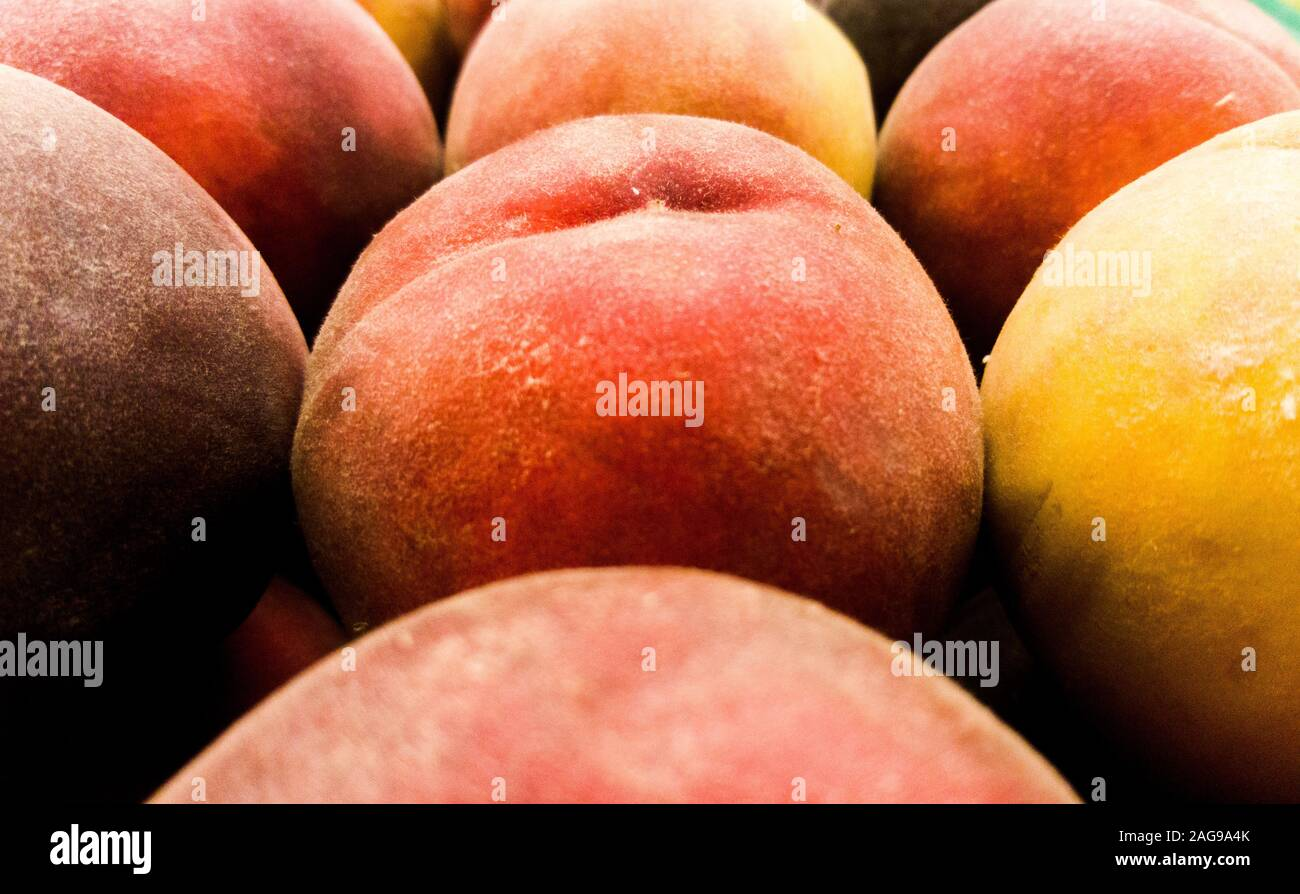 Selective focus close up on a peach fruit among others. Stock Photo