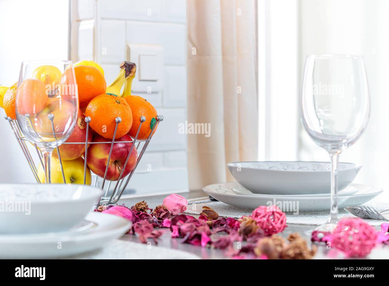 Selective focus shot of a modern table setting with flower petals, fruit and beautiful silverware Stock Photo