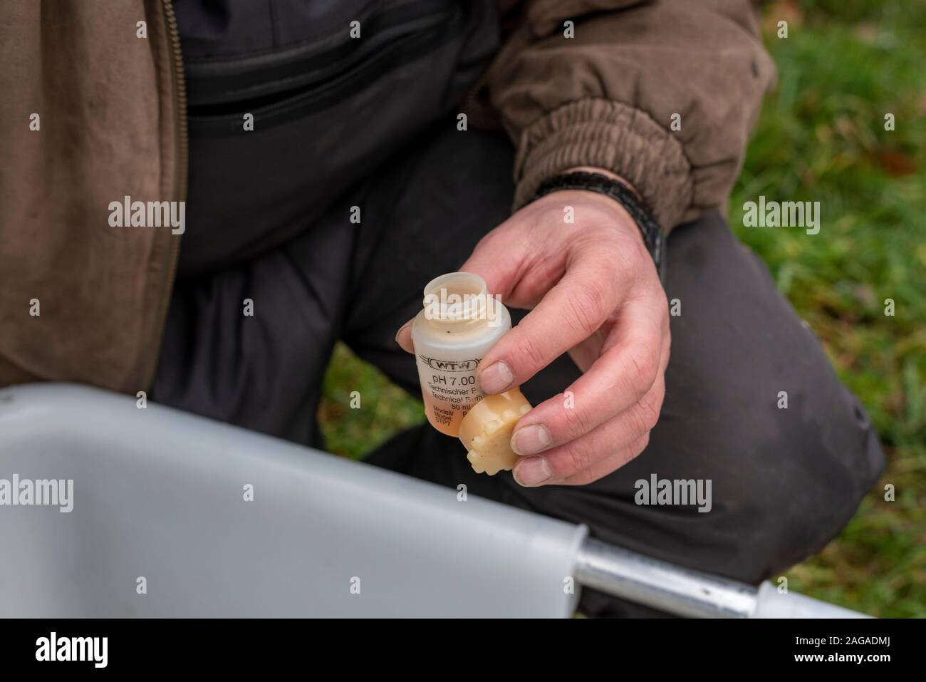 Zerbst, Saxony-Anhalt, Germany. 18th Dec 2019. Steffen Zahn from the Institute for Inland Fisheries in Potsdam (Institur für Binnenfischerei) drips an anaesthetic into a plastic tub. Salmon and sea trout are briefly anaesthetised in the liquid to measure, weigh and mark them. Zahn heads the migratory fish programme in Saxony-Anhalt. A total of 143,500 young salmon and 90,300 sea trout hatchlings have been released into the Nuthe near Zerbst over the past ten years. Credit: Mattis Kaminer/Alamy Live News Stock Photo