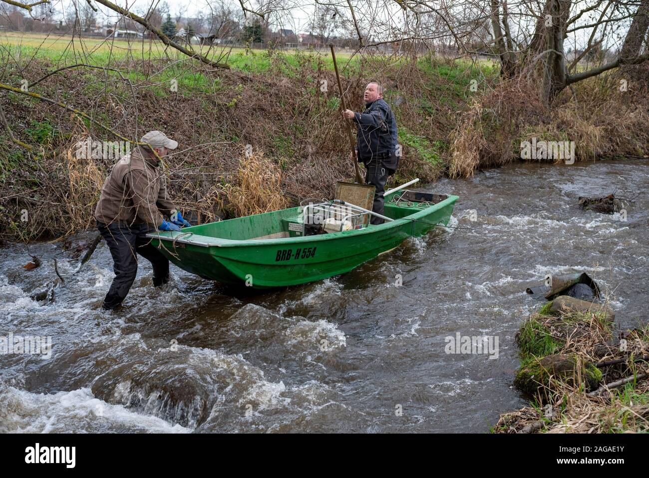 Zerbst, Saxony-Anhalt, Germany. 18th Dec 2019. Jens Winterheuser (l) and Robert Wolf from the Institute for Inland Fisheries Potsdam-Sacrow search for spawning salmon with an electric fishing gear. A total of 143,500 young salmon and 90,300 sea trout hatchlings have been released into the Nuthe near Zerbst in the past ten years. The fish migrate to the Atlantic and return to spawn in the Nuthe after a few years. Credit: Mattis Kaminer/Alamy Live News Stock Photo