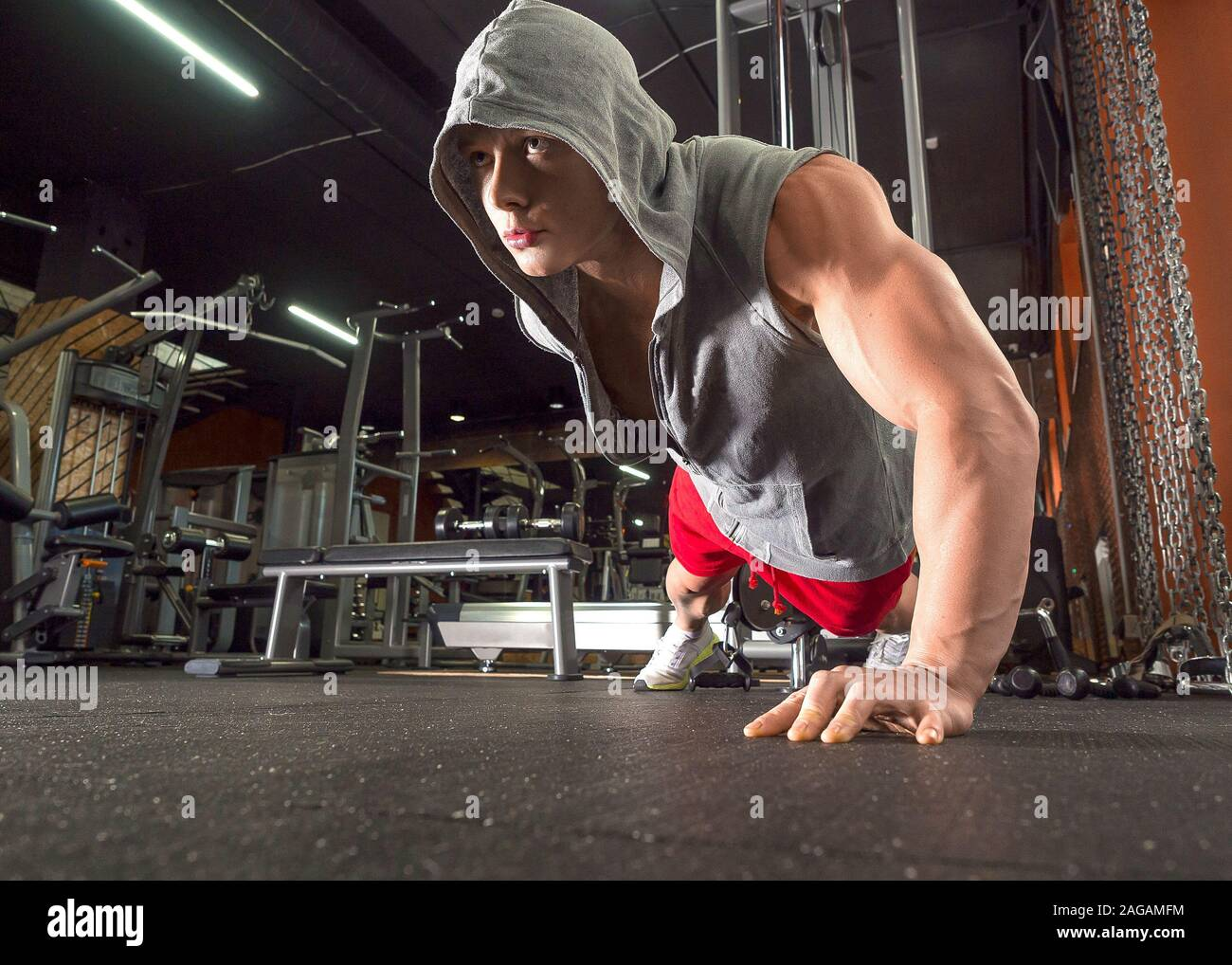 Young sporty man doing push ups exercise with one hand in fitness gym. Healty lifestyle concept Stock Photo
