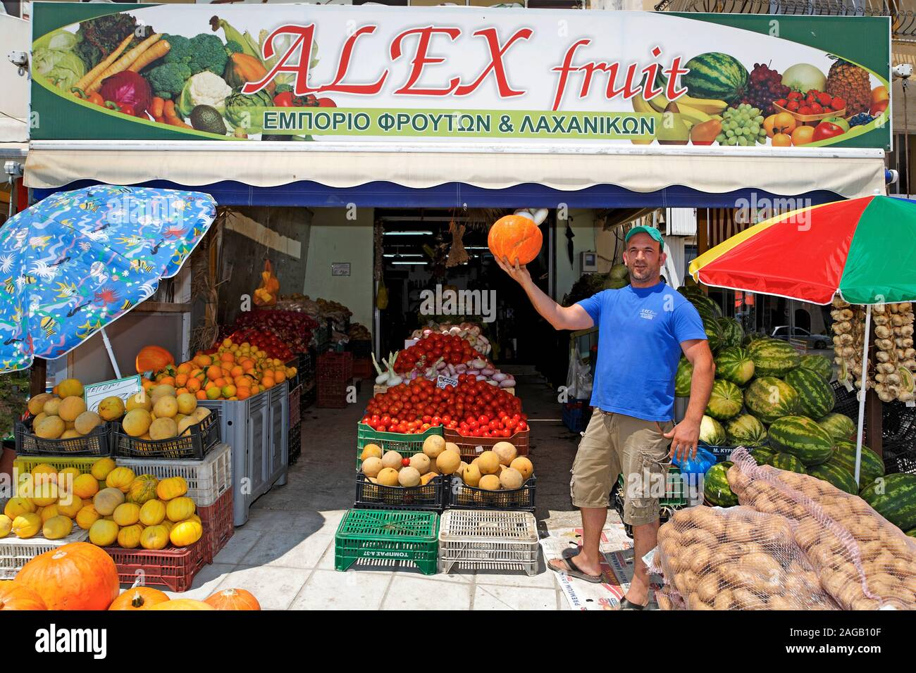 Fruit and vegetable seller shows a pumkin at his shop, Zakynthos-town, Zakynthos island, Greece Stock Photo