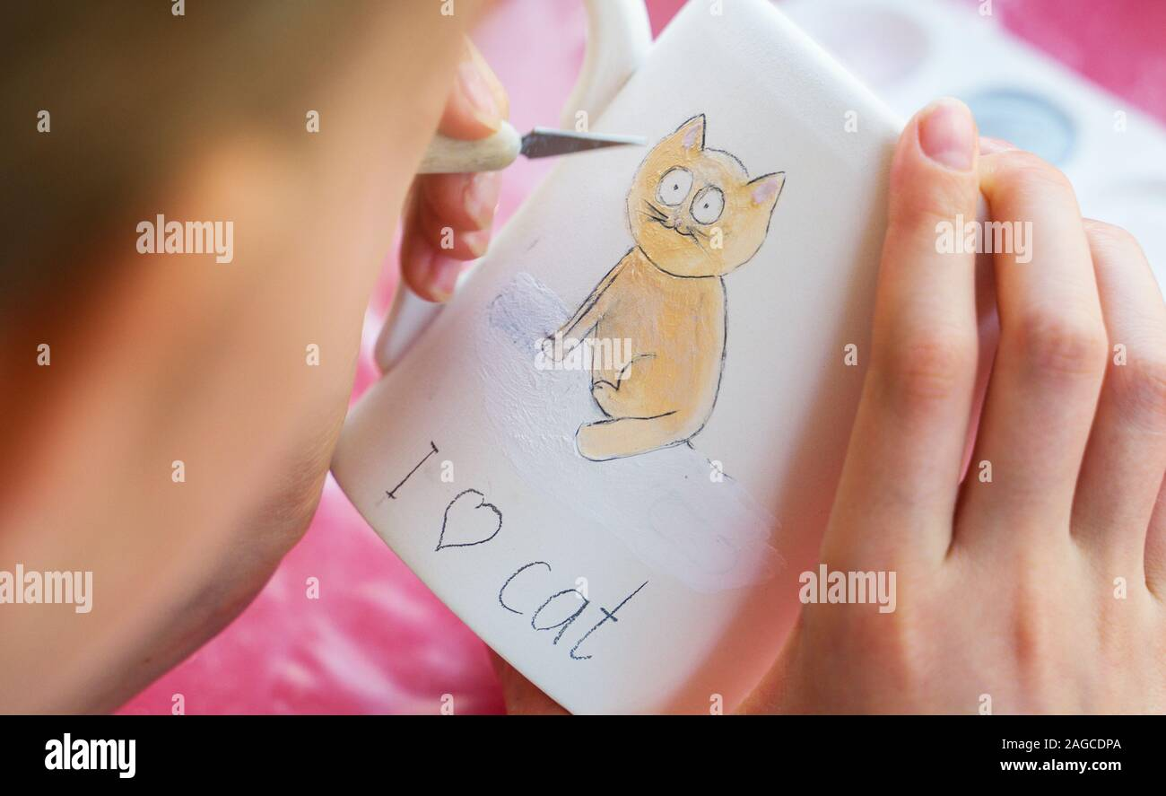 Child Paints A Mug In A Pottery Workshop Drawing A Cat Stock Photo Alamy