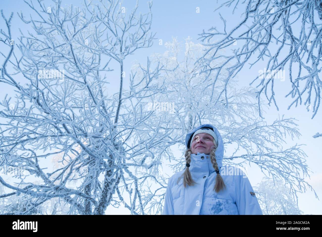 Woman outside in the snow in stylish winter suit smiling Stock Photo