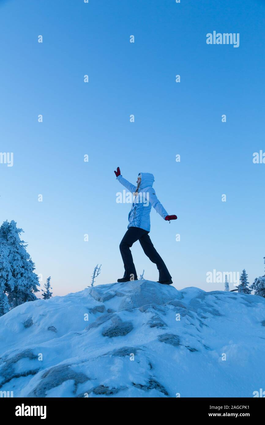 Sporty woman stretching outside surrounded by snow and ice in the winter at Koli National Park in Finland Stock Photo