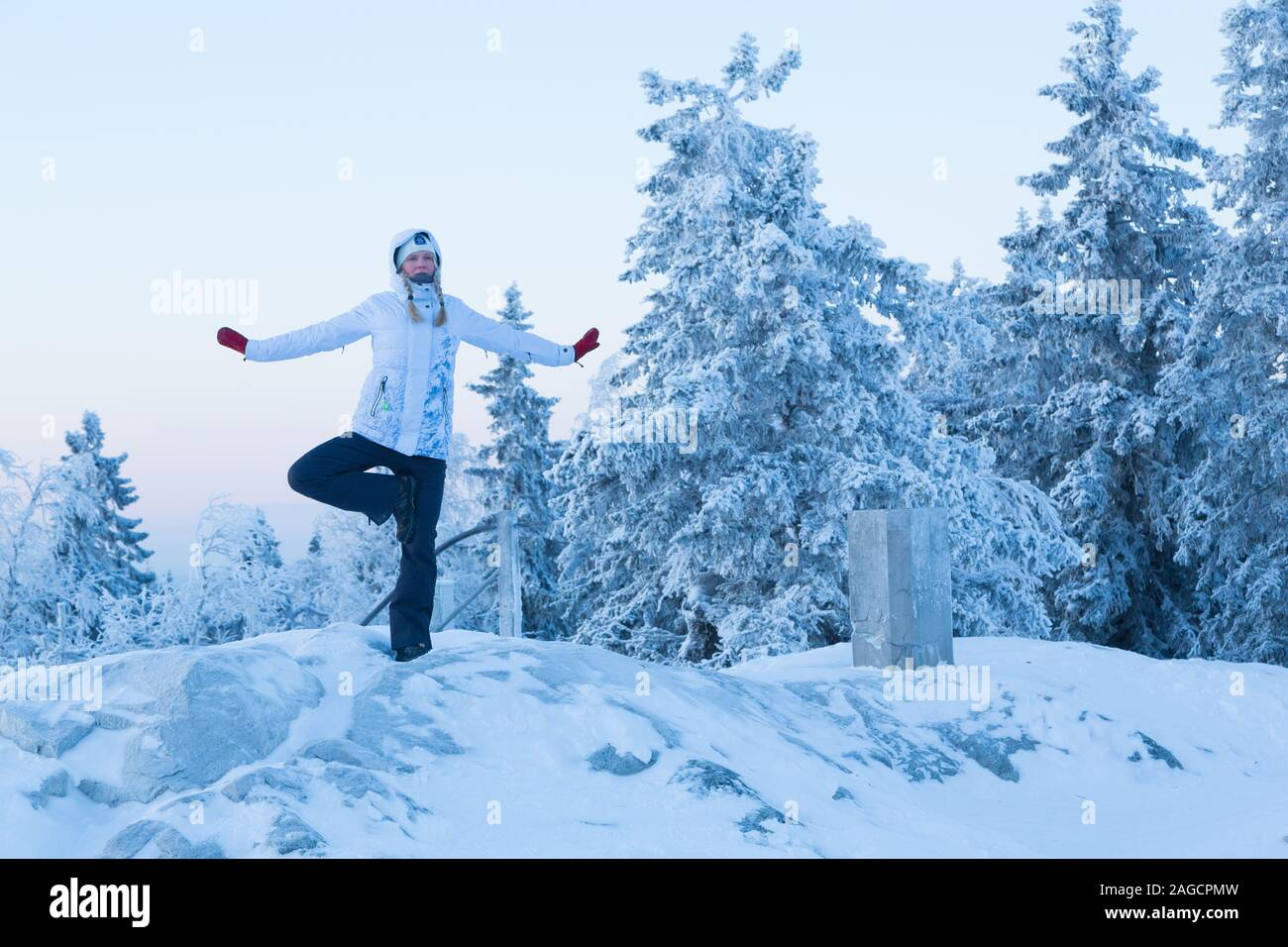 Woman doing yoga poses outside in the winter at Koli National Park Finland Stock Photo