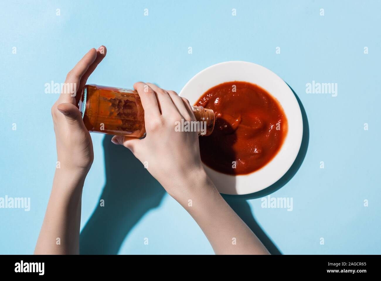 Cropped view of woman pouring tomato sauce from bottle to plate on blue background Stock Photo