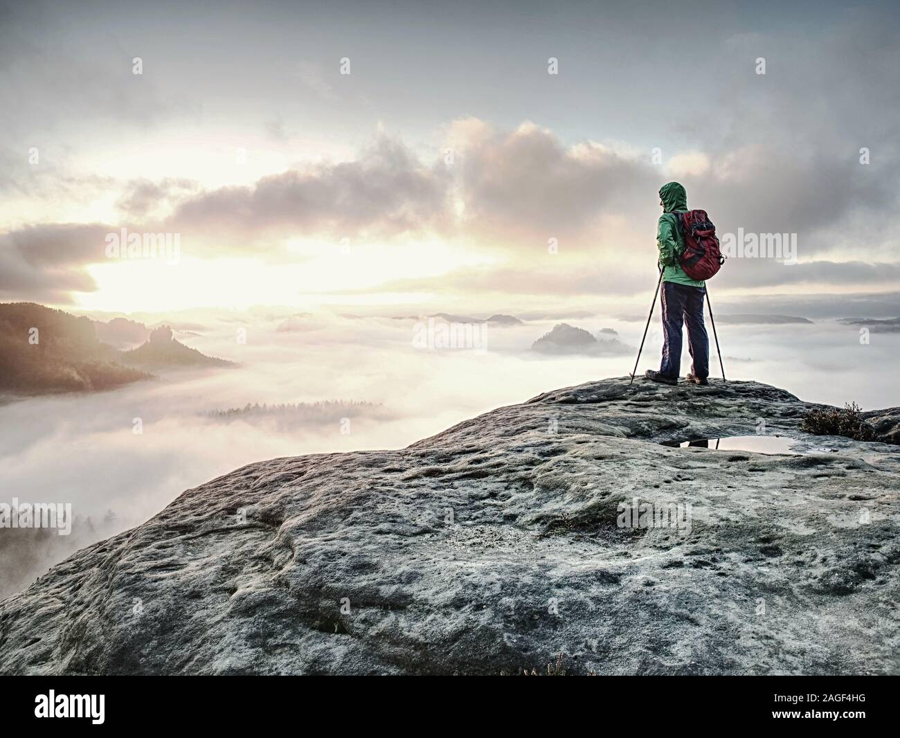 Young woman tourist standing on mountain top and looking to misty nowhere. Girl hiker alone lost in foggy cloud in high mountains. Stock Photo