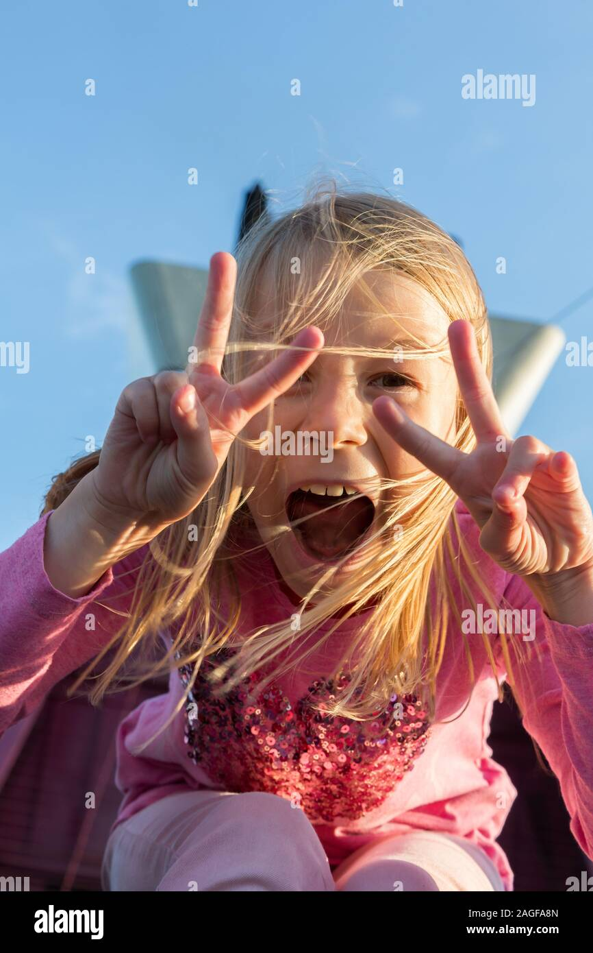 Young girl showing a victory sign smiling Stock Photo