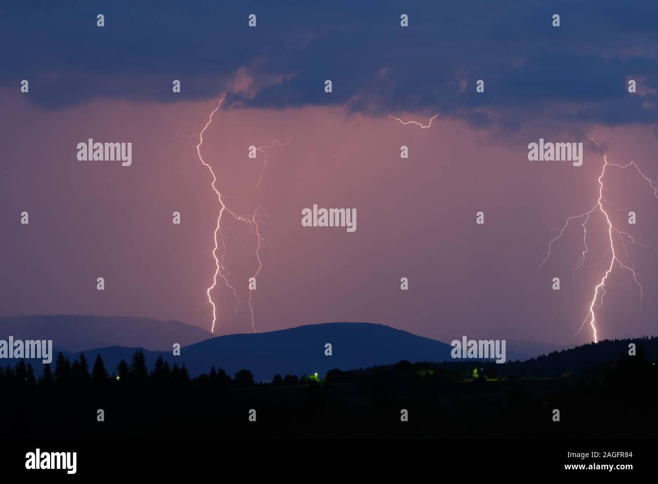 Thunderstorm with lightning on the mountain. Thunderstorms on a mountain plateau with thunderstorms after sunset. Thunderstorms and storm over pine fo Stock Photo