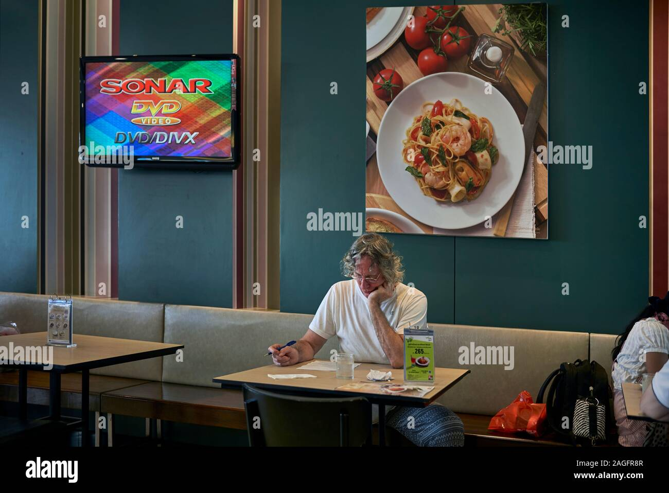 Man Alone Studying Paperwork In A Restaurant Interior Against A Wall Backdrop Of Food Art Stock Photo Alamy