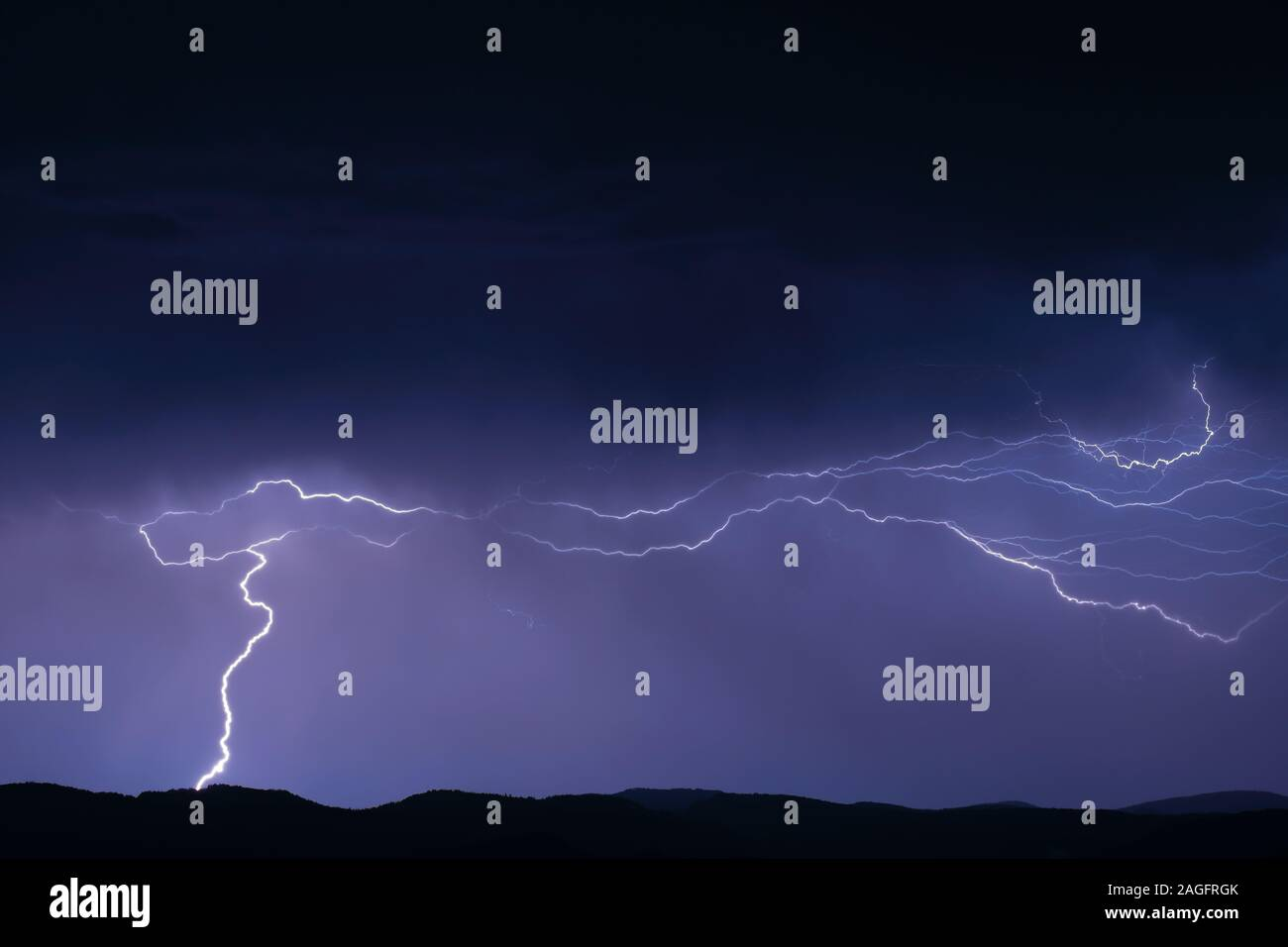 Thunderstorm with lightning on the mountain. Thunderstorms on a mountain plateau with thunderstorms after sunset. Stock Photo