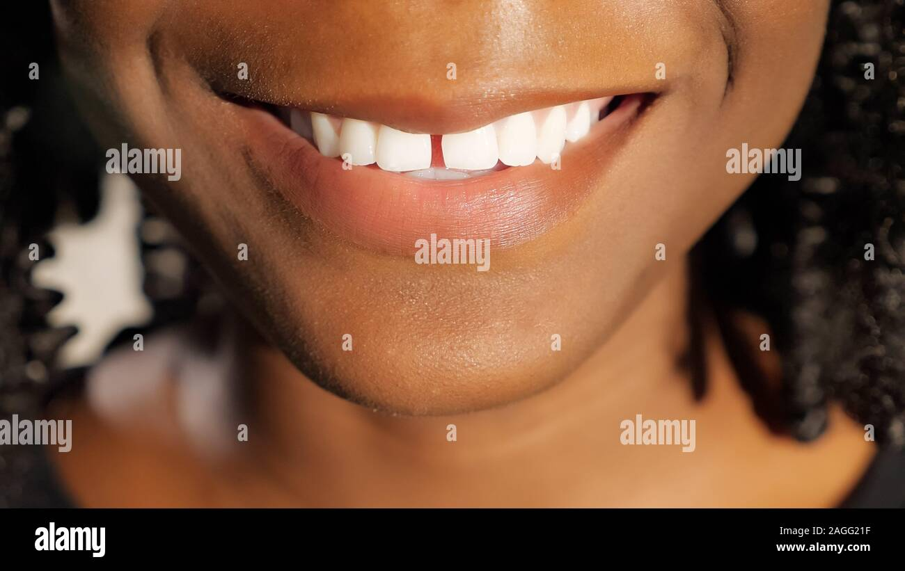 pretty young African woman with black curly hair smiles showing white teeth closeup Stock Photo