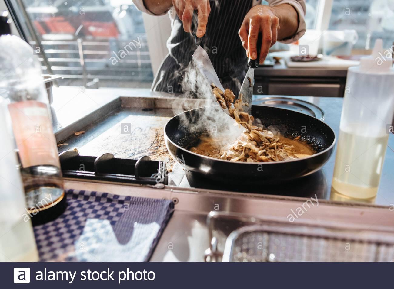 Ein Koch bereitet ein Essen mit Champignons zu Stock Photo