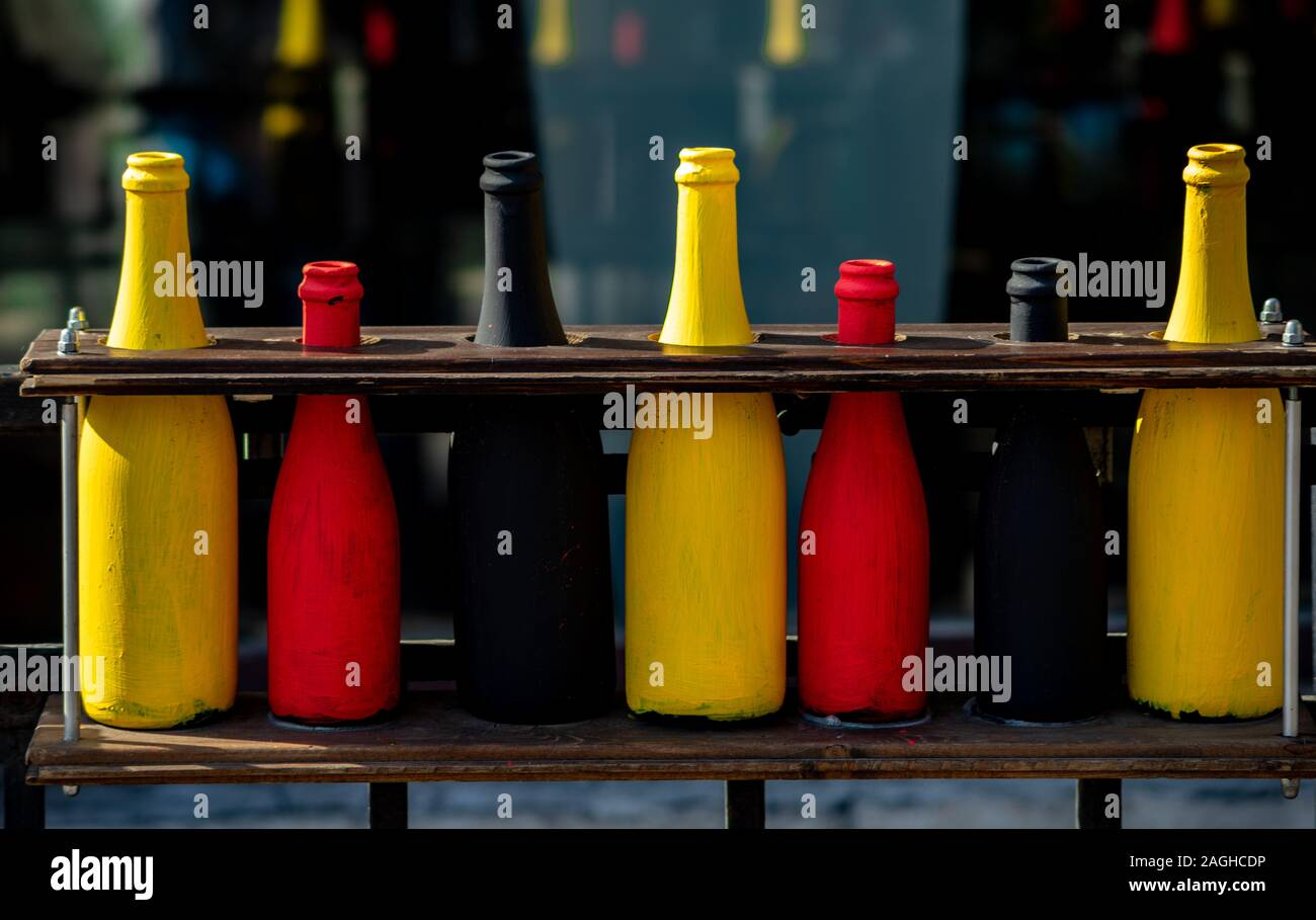 Range Of Glass Bottles Painted Red Black And Yellow Paint Stock Photo Alamy