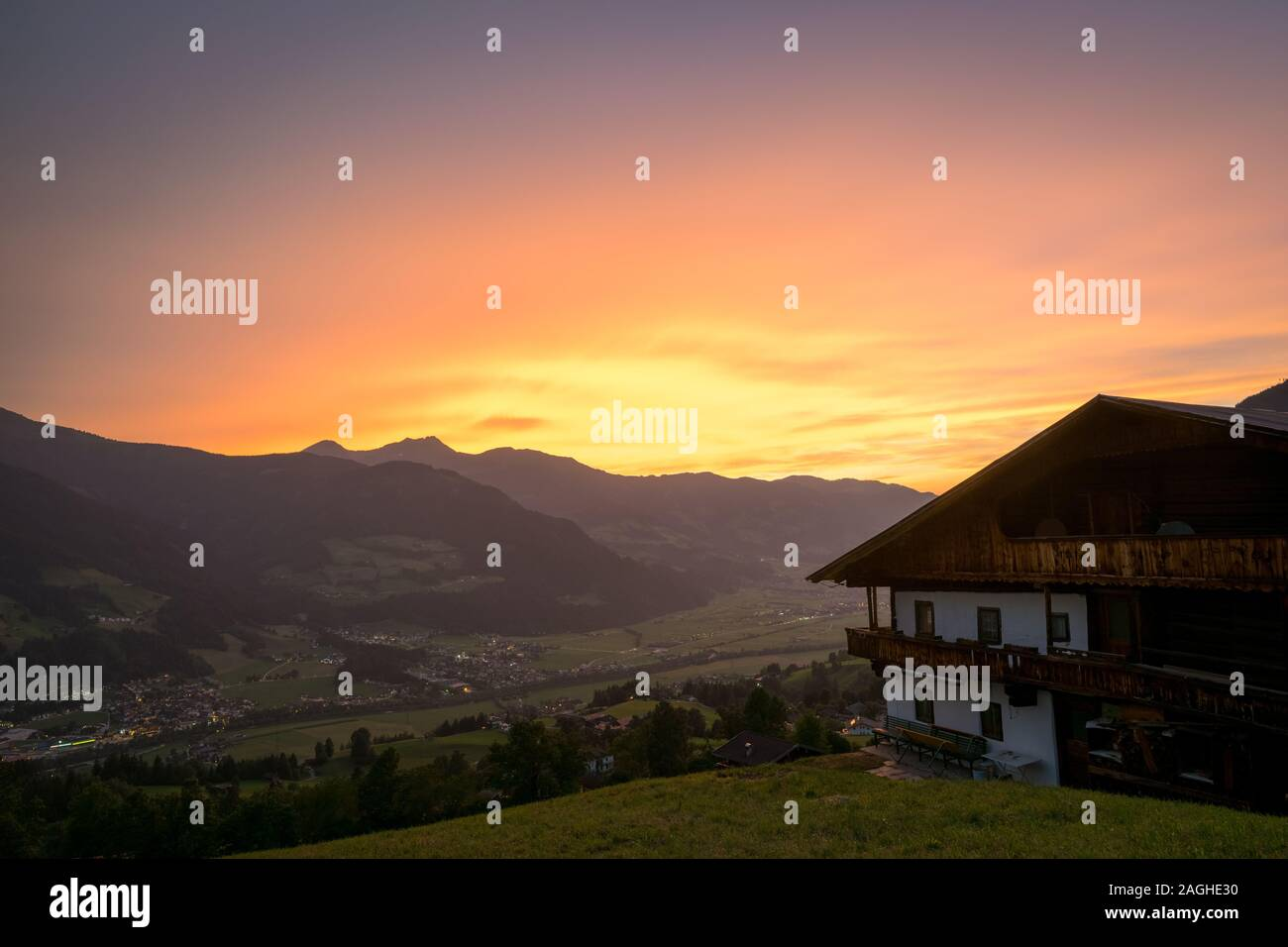 """Beautiful sunset over the valley """"Zillertal"""" in Tirol, Austria. Typical austrian cottage in the foreground. Stock Photo"""
