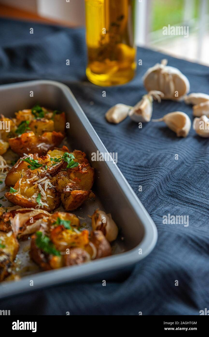 Freshly baked potatoes in a oven tray with fresh garlic and olive oil Stock Photo