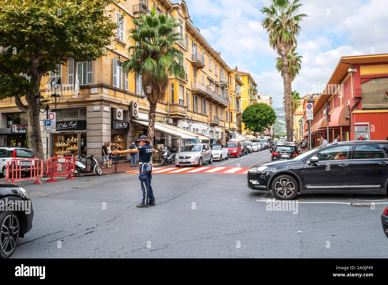 A female policewoman directs traffic at a red and white crosswalk in the urban center of Ventimiglia, on the Italian Riviera. Stock Photo