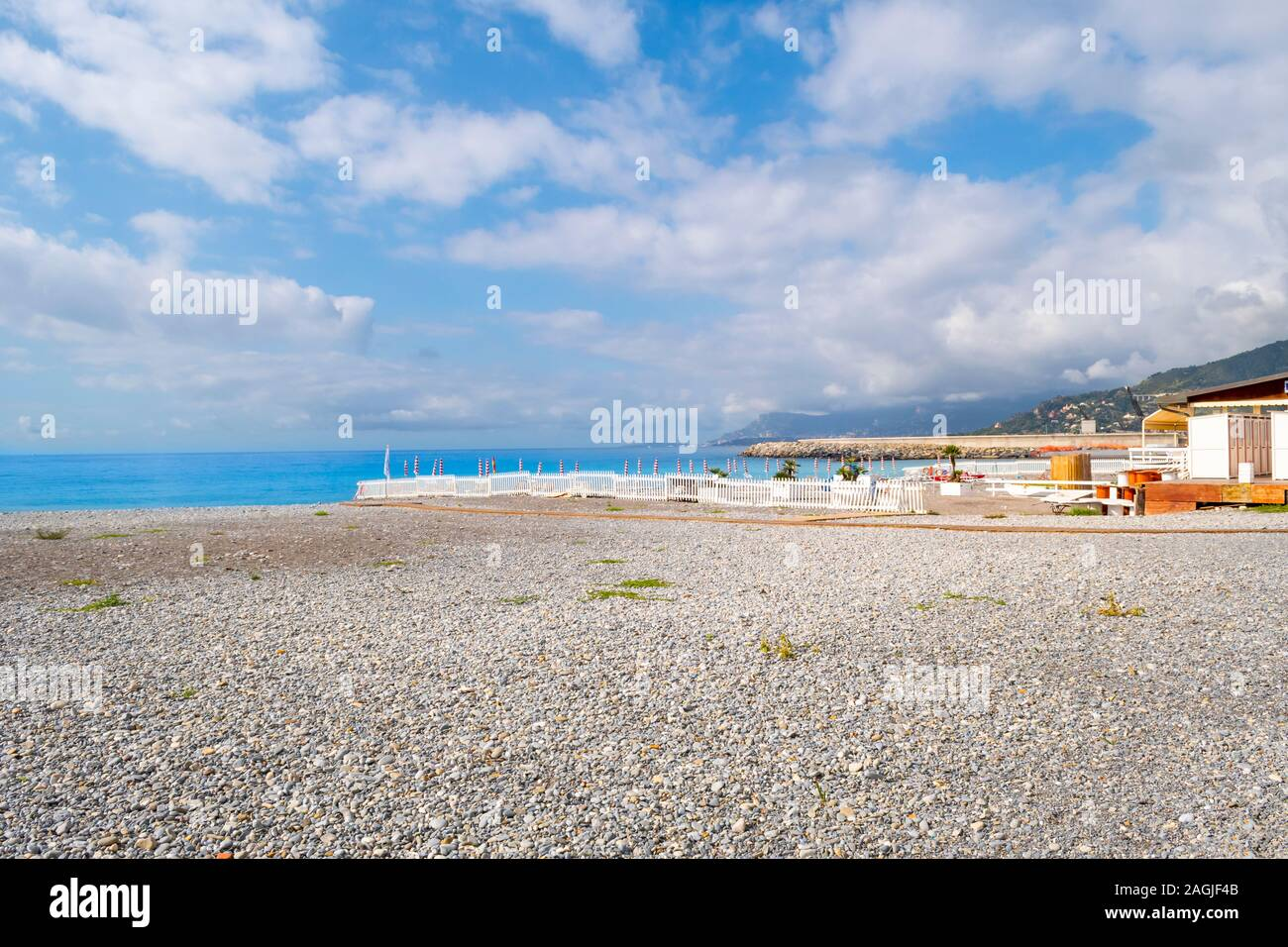 The blue Mediterranean sea, private pebble beach and seaside town of Ventimiglia, Italy, on the Italian Riviera Stock Photo