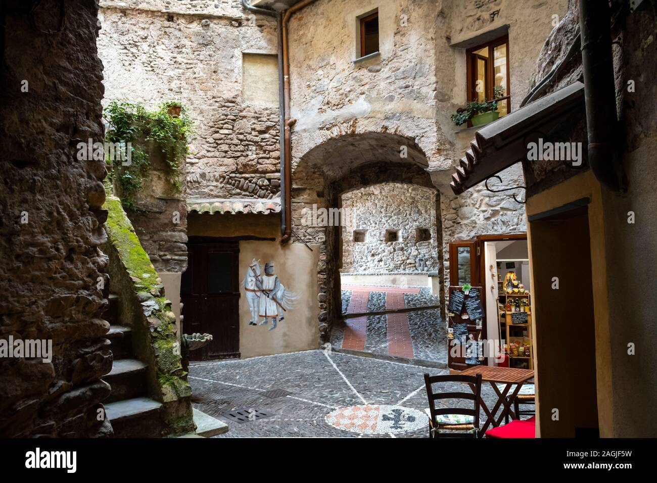A picturesque courtyard with medieval knight images and gift shop in the ancient center of the medieval hilltop village of Dolceacqua, Italy Stock Photo