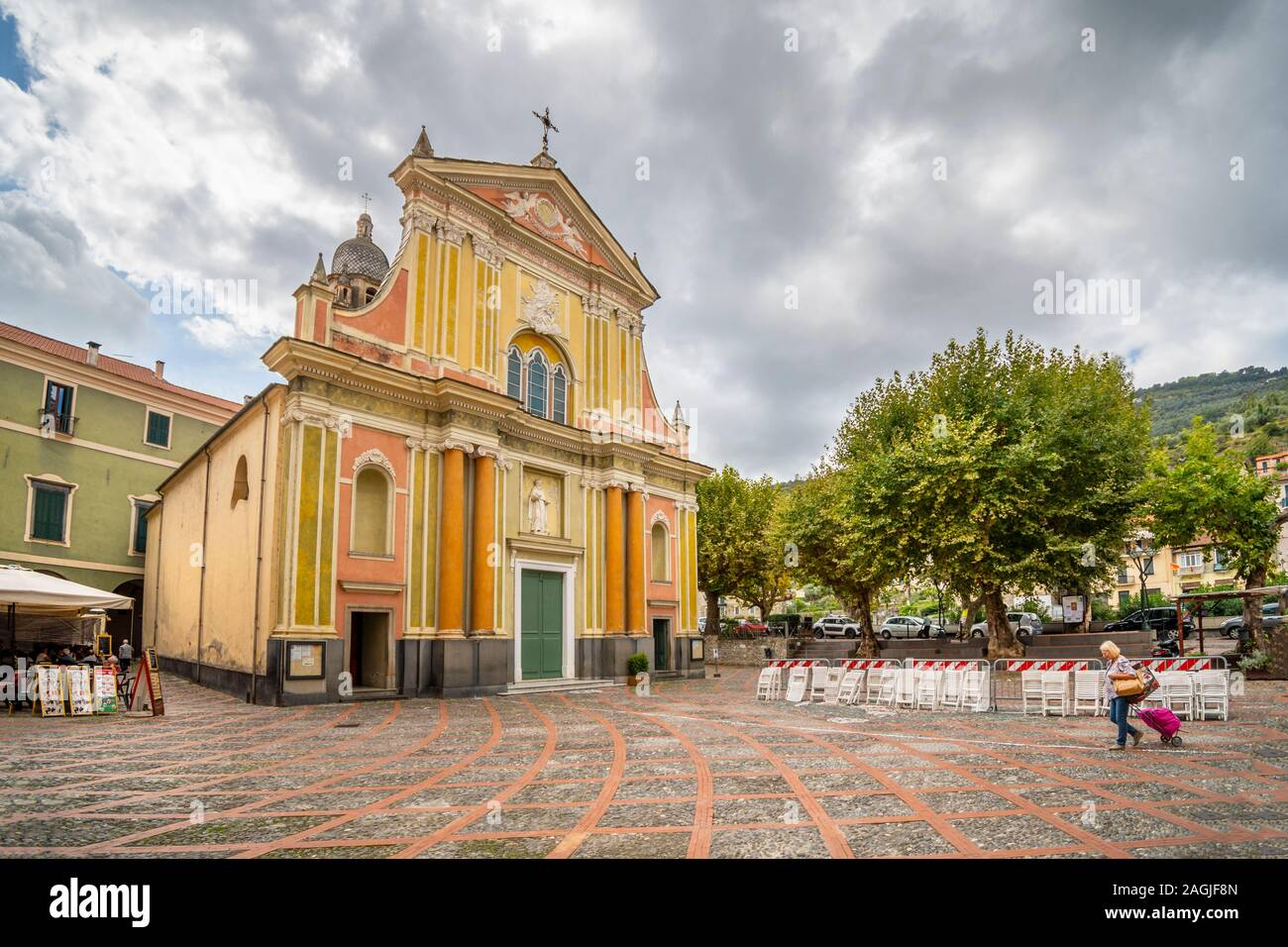 A tourist passes by the Sant Antonio Abate Church in a small piazza on an overcast day in Dolceacqua, Italy Stock Photo
