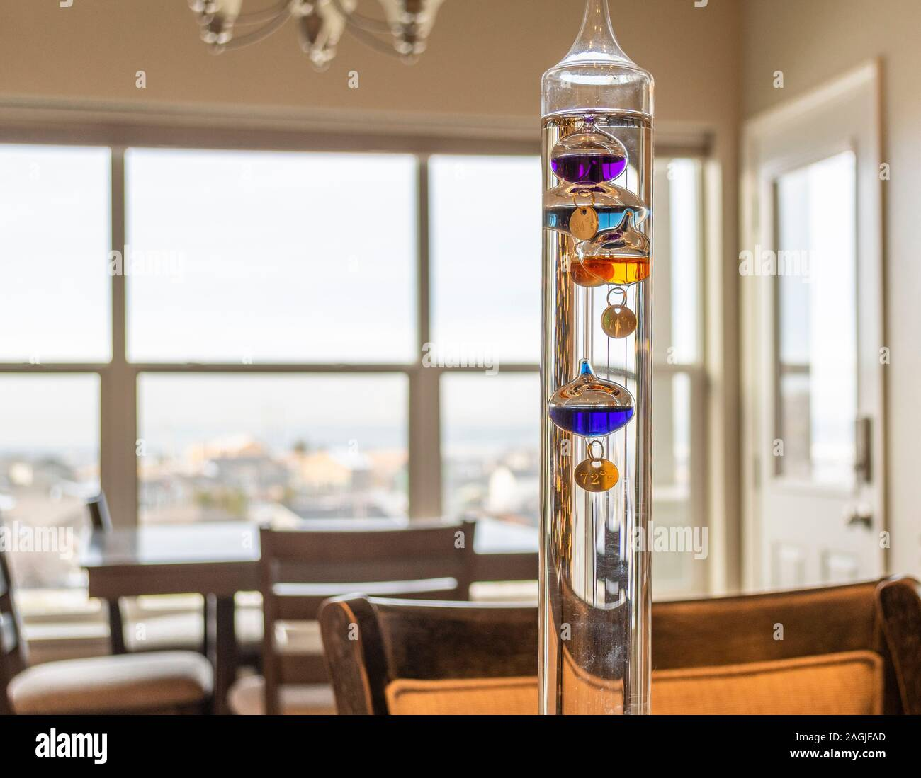 A colorful, glass, liquid filled Galileo Thermometer measures indoor temperature in a room with a view. Stock Photo