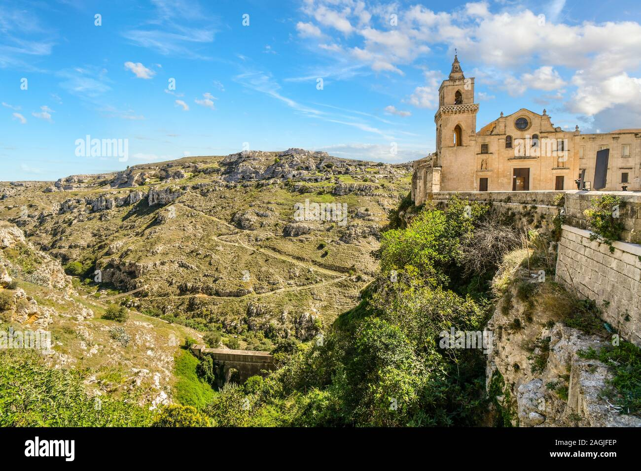 Paths from the ancient sassi caves cut down the mountainside and into the canyon in Matera, Italy, as the San Pietro Caveoso Church sits atop a cliff Stock Photo