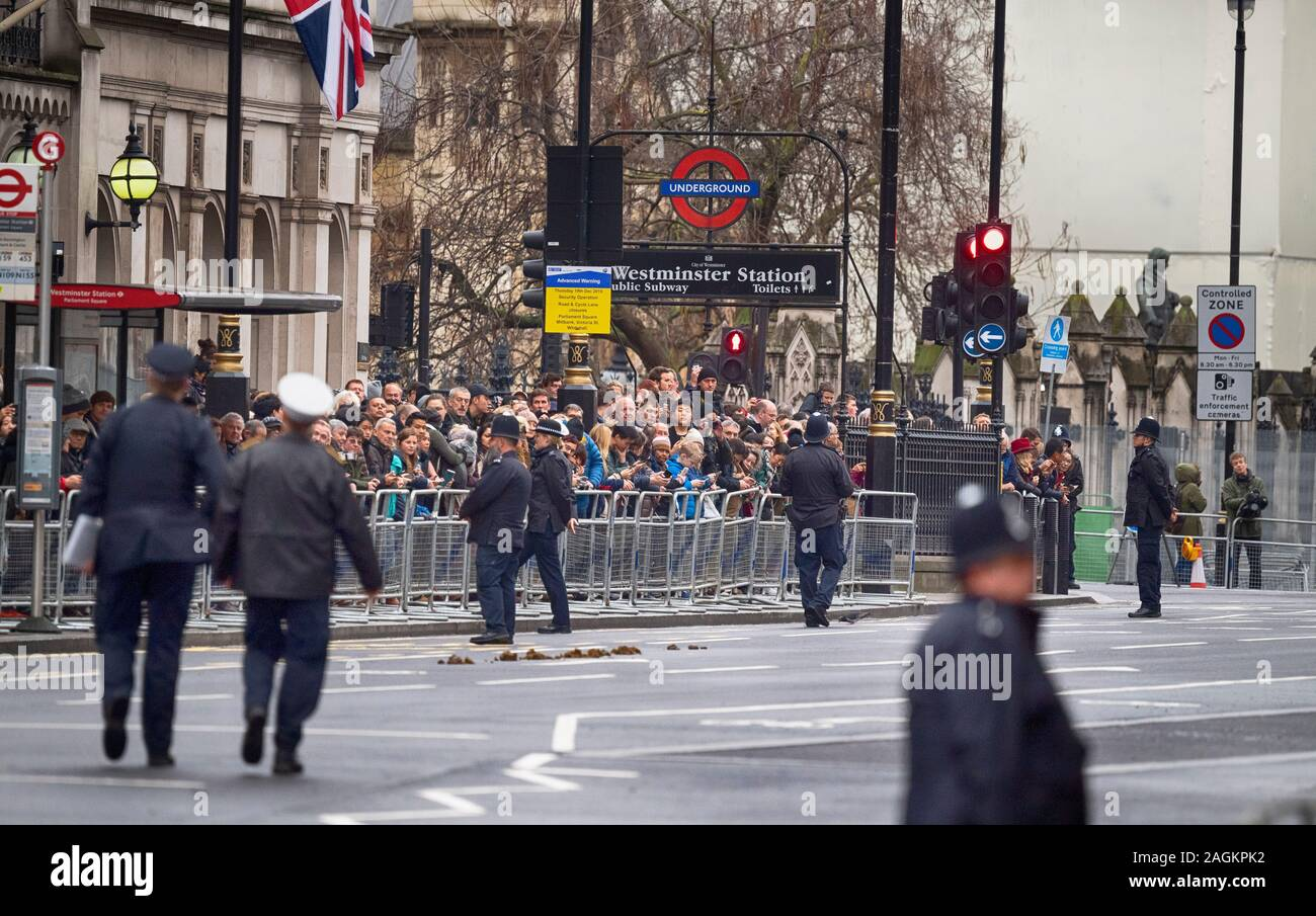 Whitehall, London, UK. 19th December 2019. Road closures in Westminster and heavy police security as people gather to watch The Queen accompanied by Prince Charles arriving to attend the State Opening of Parliament. Credit: Malcolm Park/Alamy. Stock Photo