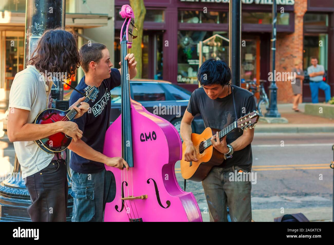 Young musicians at a street corner in downtown Ann Arbor playing a guitar, acoustic bass and a mandolin. Stock Photo