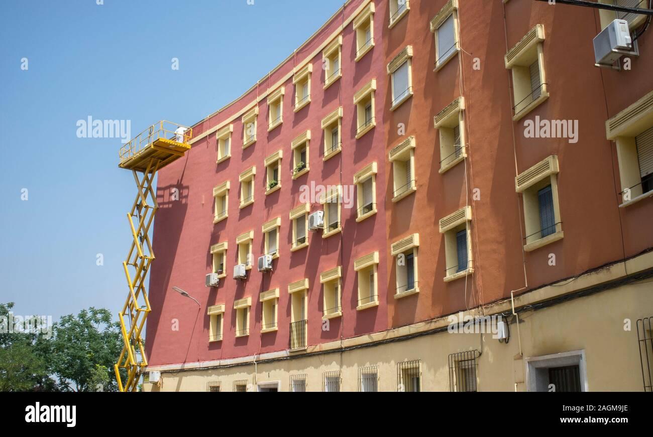 Painter working over scissor lift platform. Urban background over blue sky Stock Photo