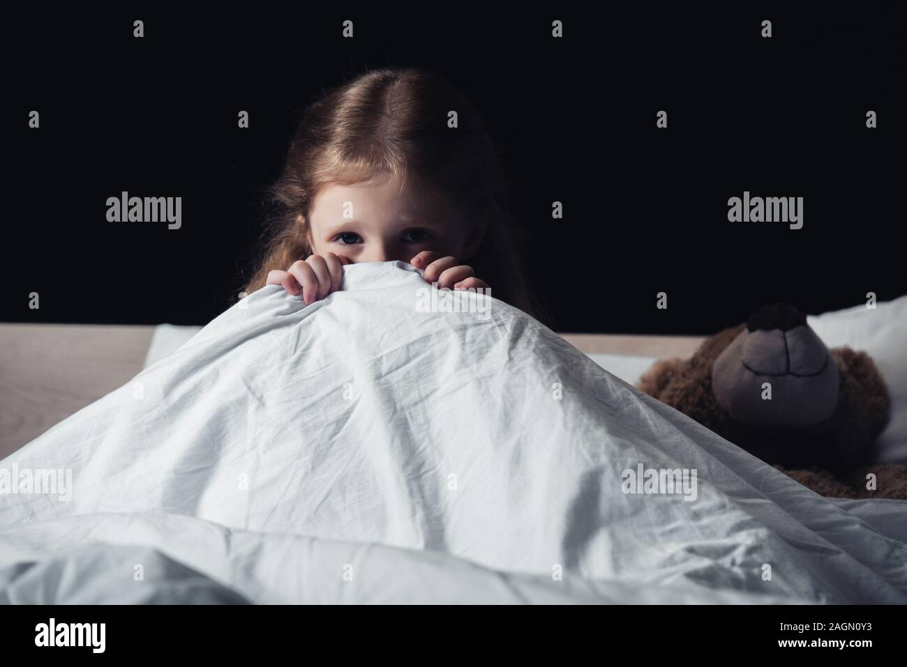 Scared Child Hiding Under Blanket While Sitting On Bedding Near Teddy Bear Isolated On Black Stock Photo Alamy