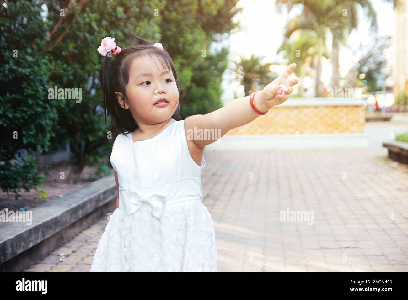 Liitle asian girl standing and poiting finger to the right. Future children concept. Stock Photo