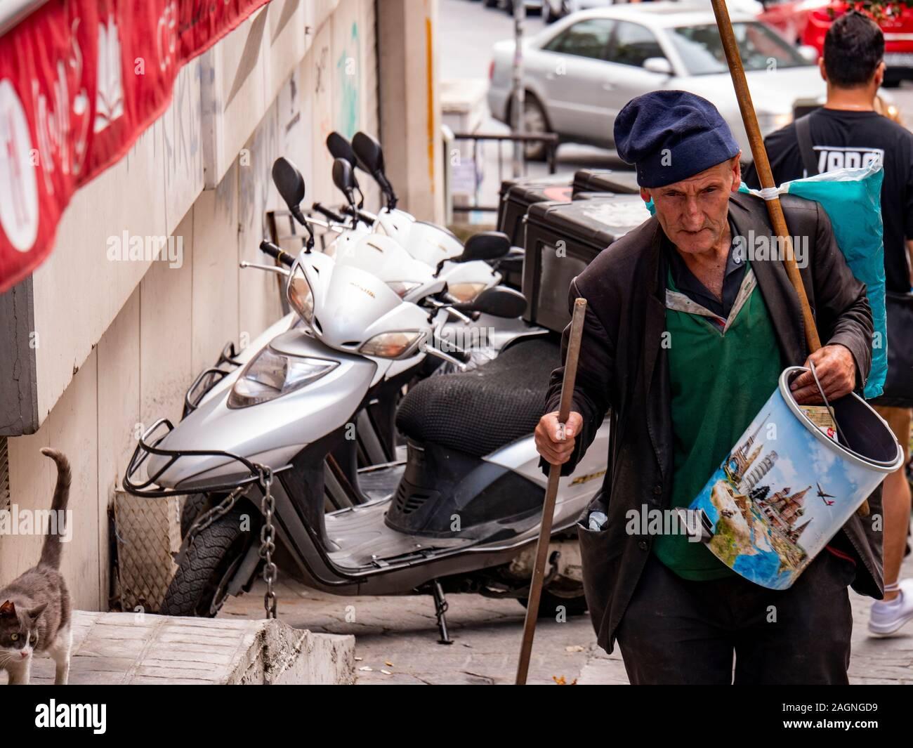Istanbul , Turkey ; October 2019 : Old peddle man walking wooden cane sidewalk in Istanbul's street sidewalk Stock Photo
