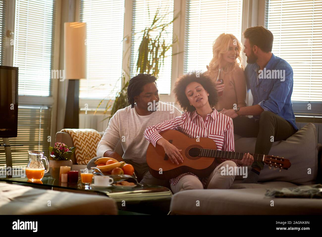 Young girl play on guitar and friends listening her Stock Photo