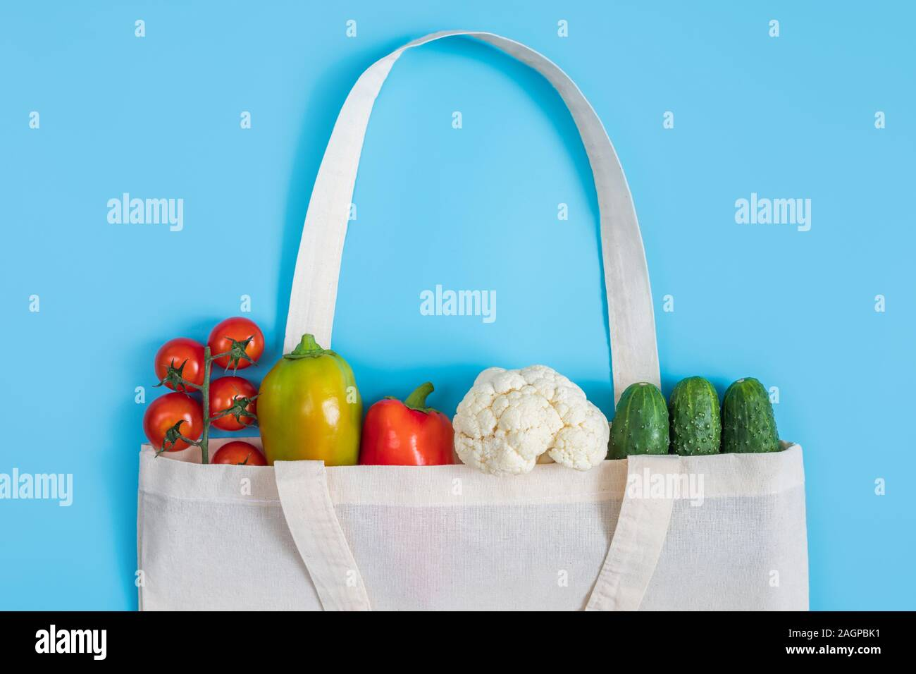 Zero waste concept. Vegetables in eco friendly reusable textile bag on blue background. Plastic free. Healthy fresh vegetarian food. Flat lay Stock Photo