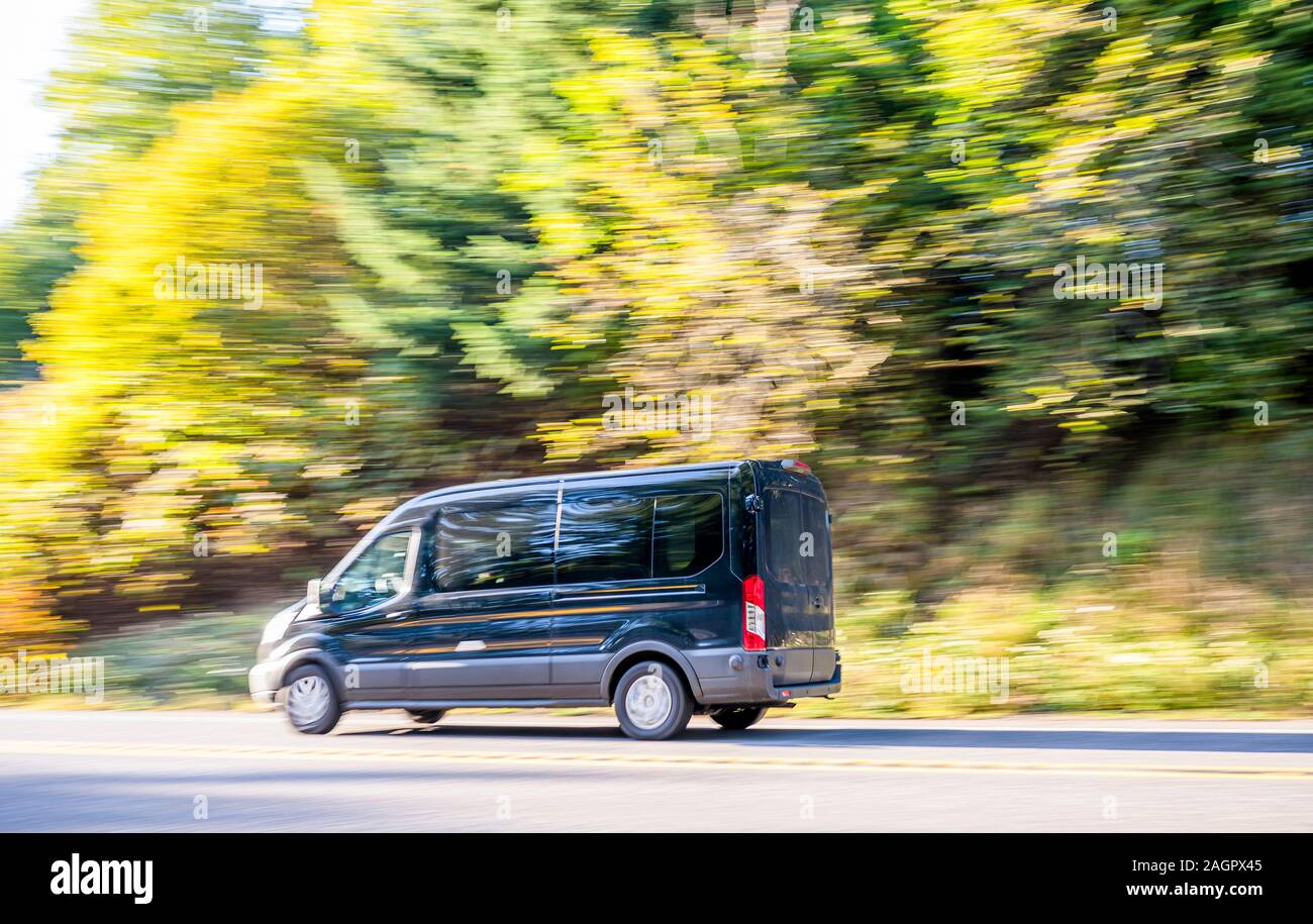 Black comfortable compact commercial cargo mini van for local freight and deliveries and small business needs running on autumn road with green and ye Stock Photo