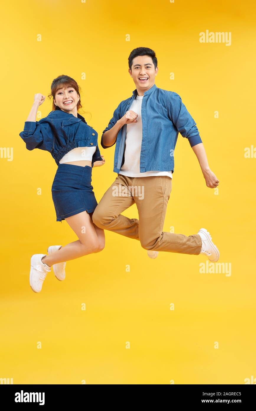Full length body size view of nice attractive lovely cheerful cheery couple jumping up in air isolated over yellow background Stock Photo