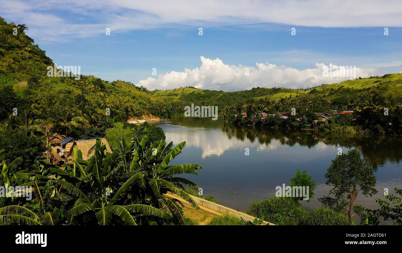 River and green hills. Beautiful natural scenery of river in southeast Asia. Countryside on a large tropical island. Small village on the green hills by the river. The nature of the Philippines, Samar Stock Photo