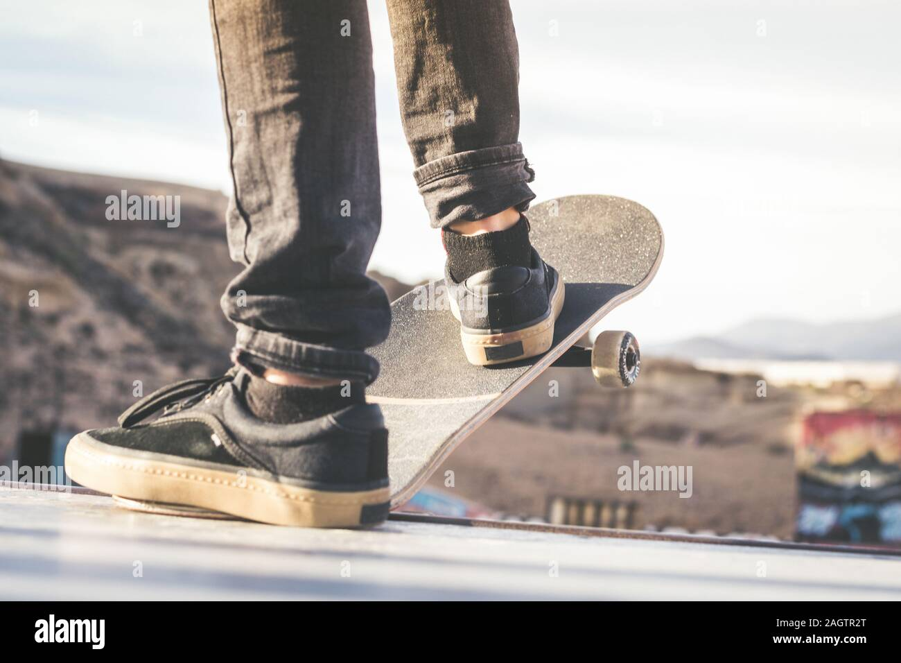 Close up view of teen's feet on a skateboard ready to start a ride over the half pipe. Skater starting jumps and tricks at the skate park. Let's go en Stock Photo