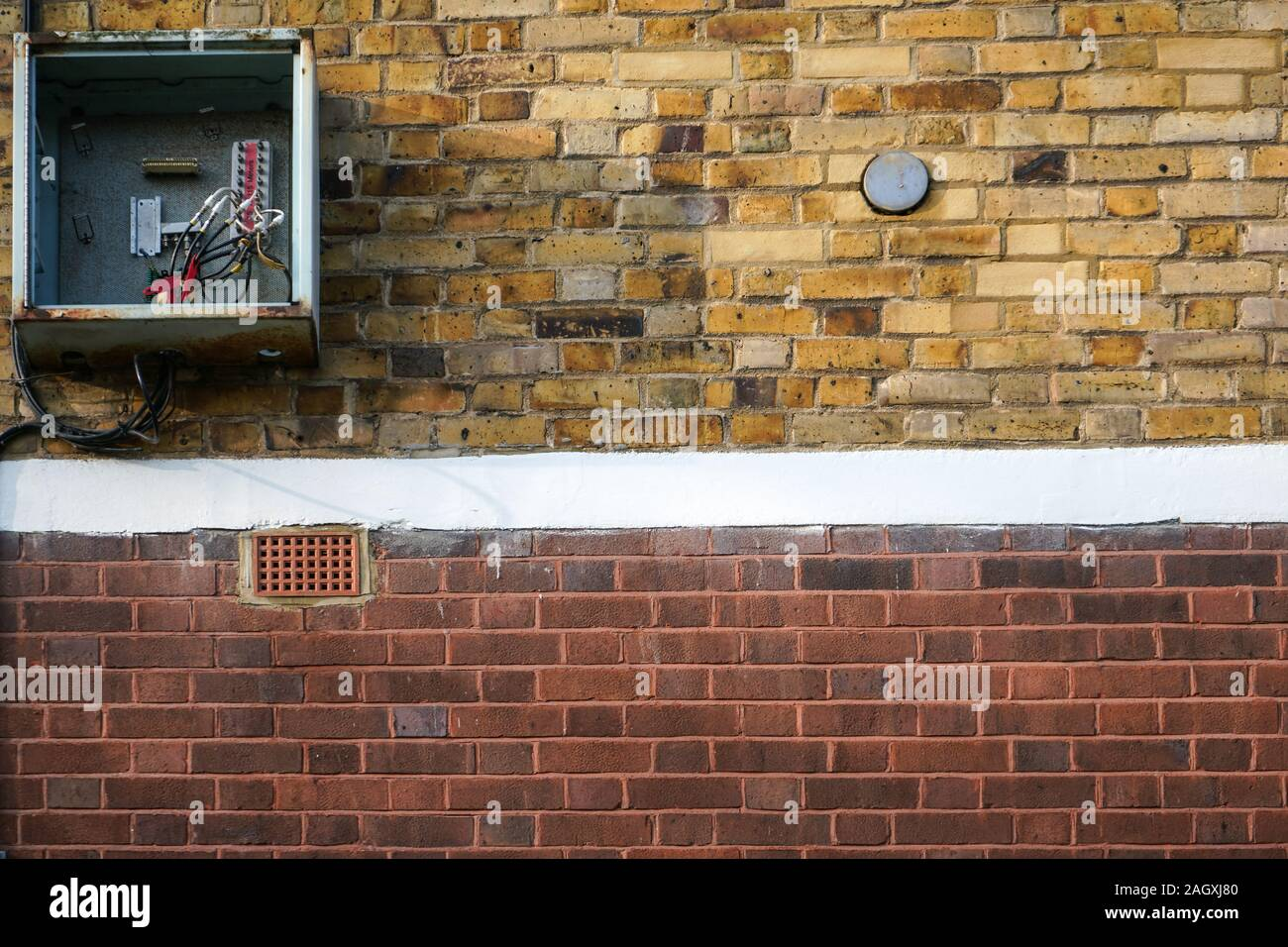 Bricks wall, with electricity / fuse box on it, opened, cover missing, cables visible. Stock Photo