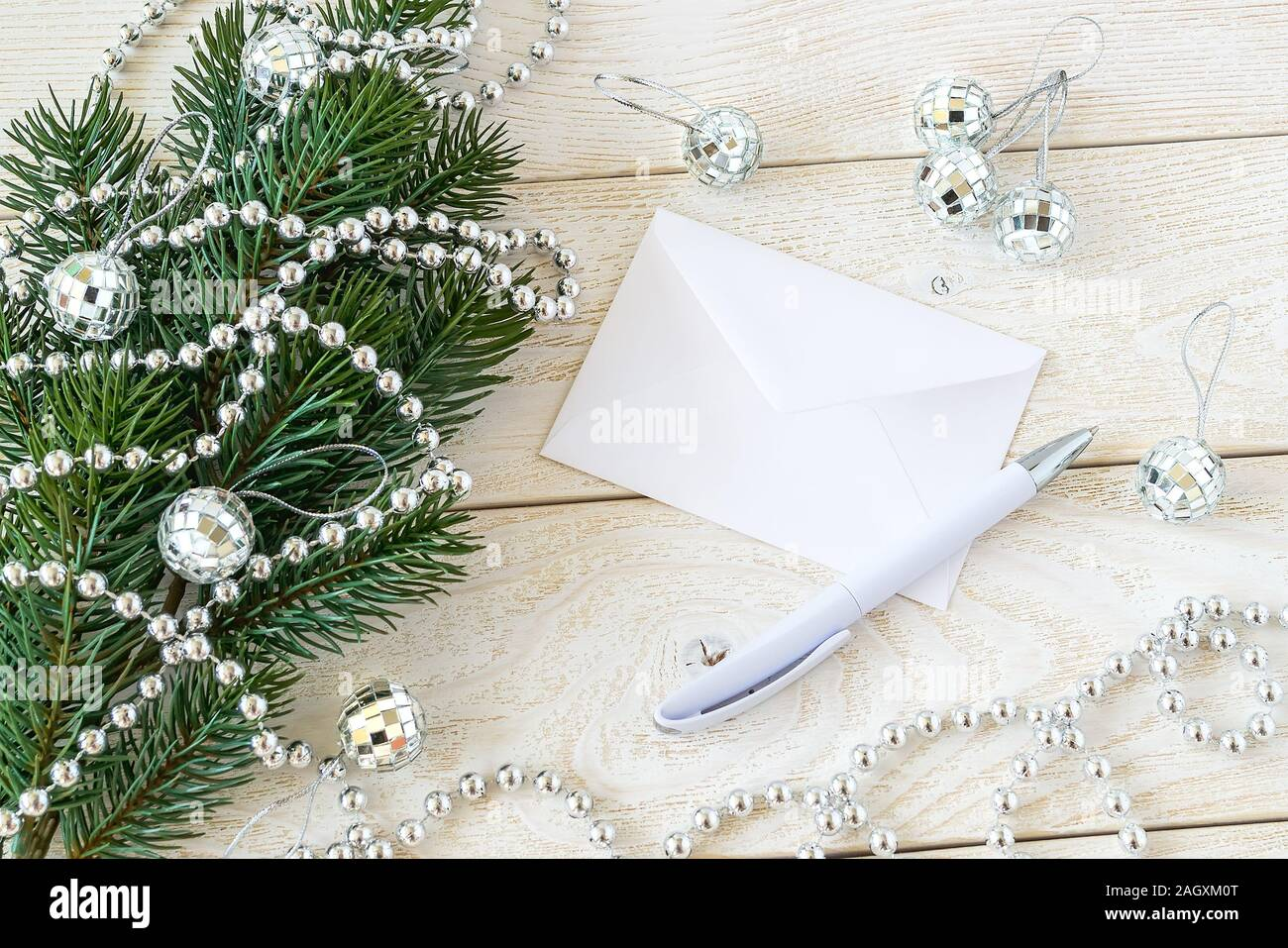 White Envelope And Ballpoint Pen On A Wooden Table Near A Fir Branch With Silver Bead Garland And Mirror Christmas Balls Greeteing Card For New Year Stock Photo Alamy