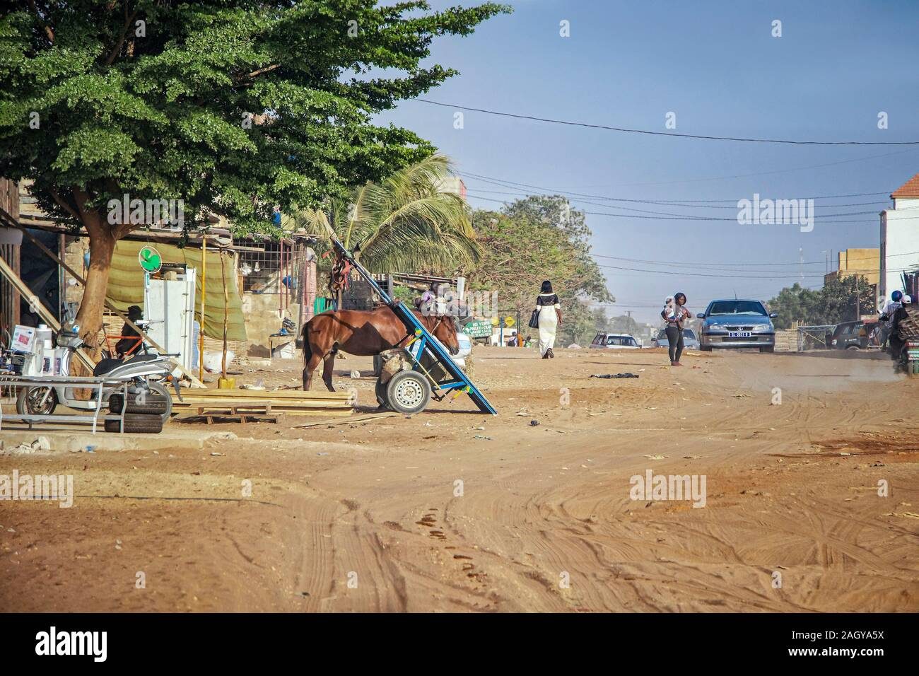 Mbour, SENEGAL - APR 26, 2019: Unidentified Senegalese woman with baby are walking down a dusty road in the middle of the city. There's a car on the Stock Photo
