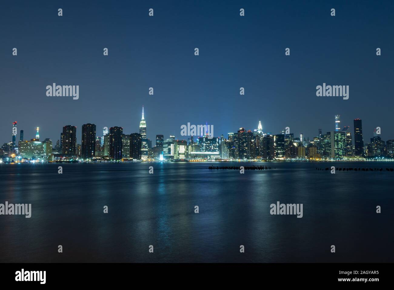 Long time exposure of New York City Manhattan midtown skyline at night viewed from Transmitter Park Stock Photo