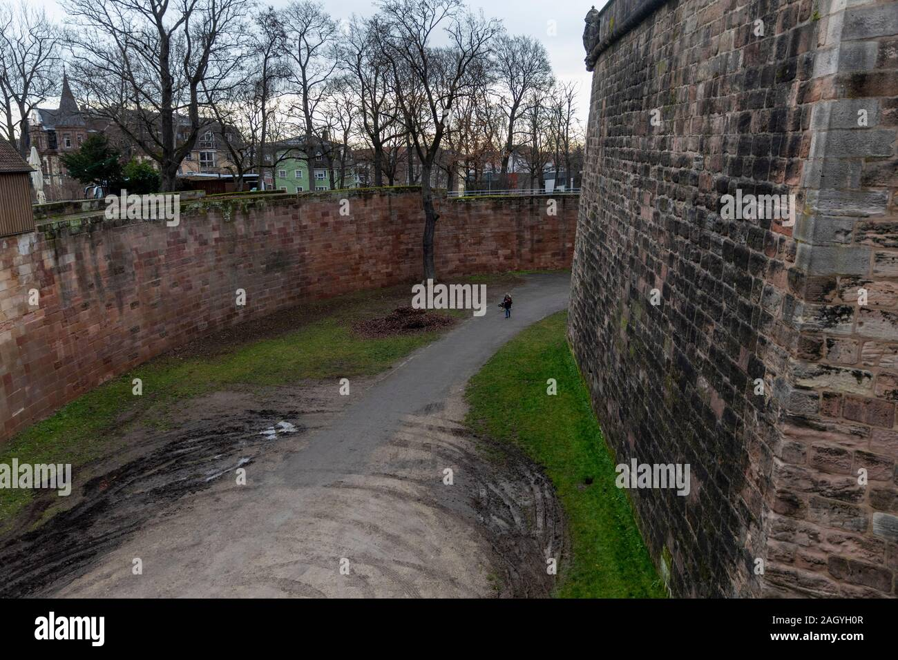 Nuremberg historical castle is very well preserved. Person walking the dog gives comparison to the amazing height of defensive wall. Stock Photo