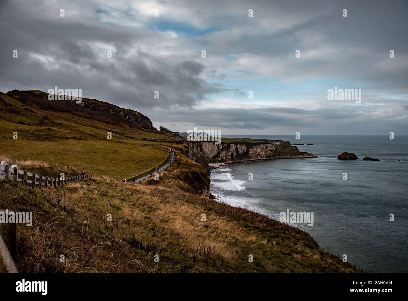 People walking along the coastal pathway during a rainy, cold and cloudy day on the cliffs near Ballintoy in Northern Ireland. Stock Photo