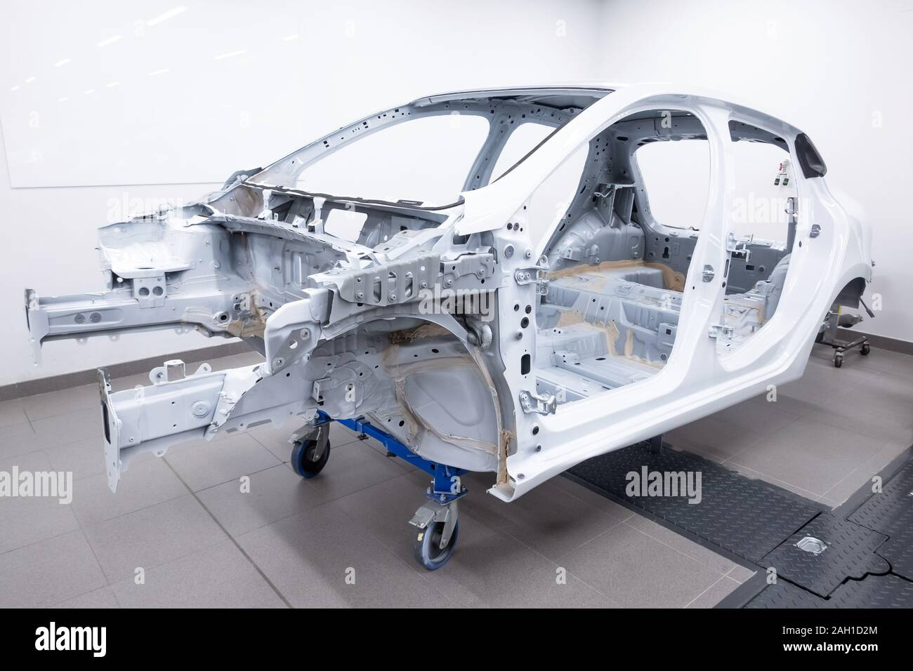 Custom car being build in workshop. Sports car body, car frame is assembled by mechanics. Metallic auto chassis in the air, car skeleton in service Stock Photo