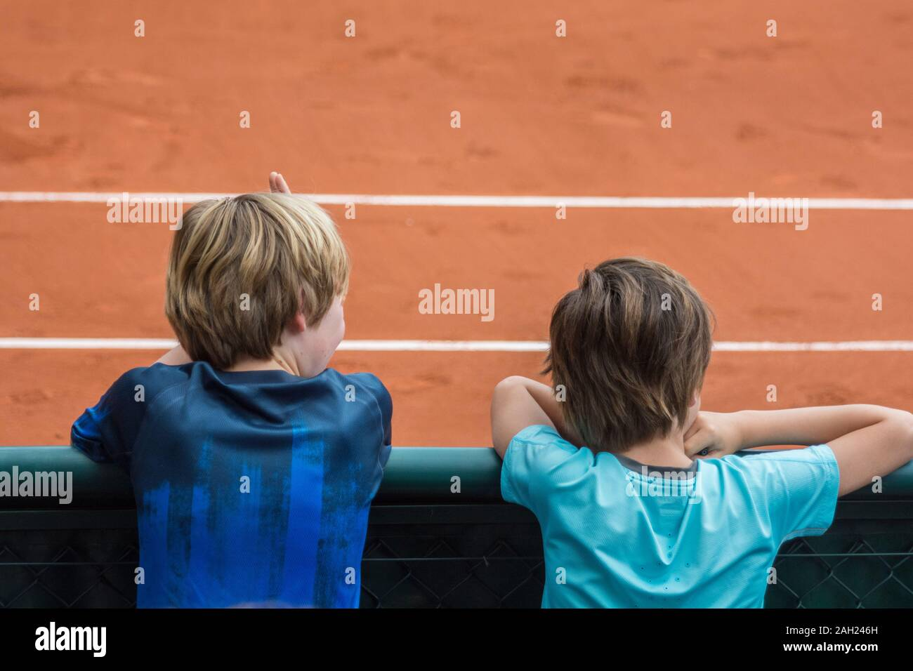 Two kids, facing backwards, watching a Tennis game in a clay court, during the French open tournament, officially  Roland-Garros, Paris, France Stock Photo