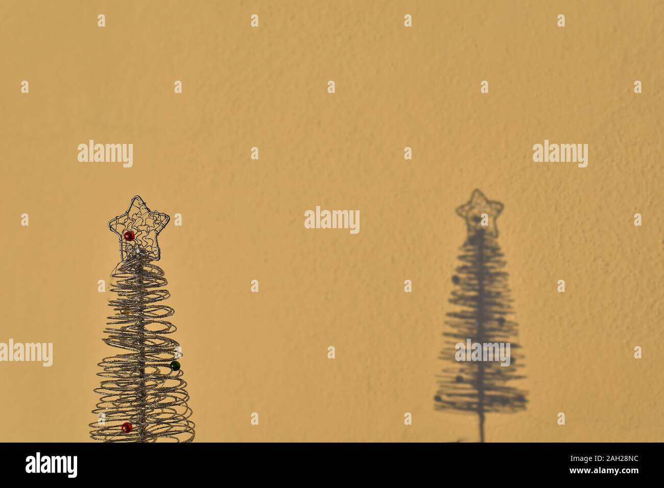 Small Christmas Tree And Its Shadow Cast By The Evening Light On A Yellow Wall Stock Photo Alamy